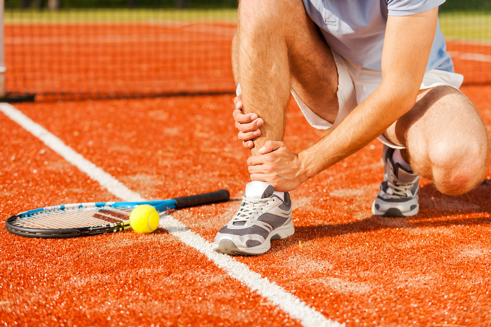 Sports injury. Close-up of tennis player touching his leg while sitting on the tennis court